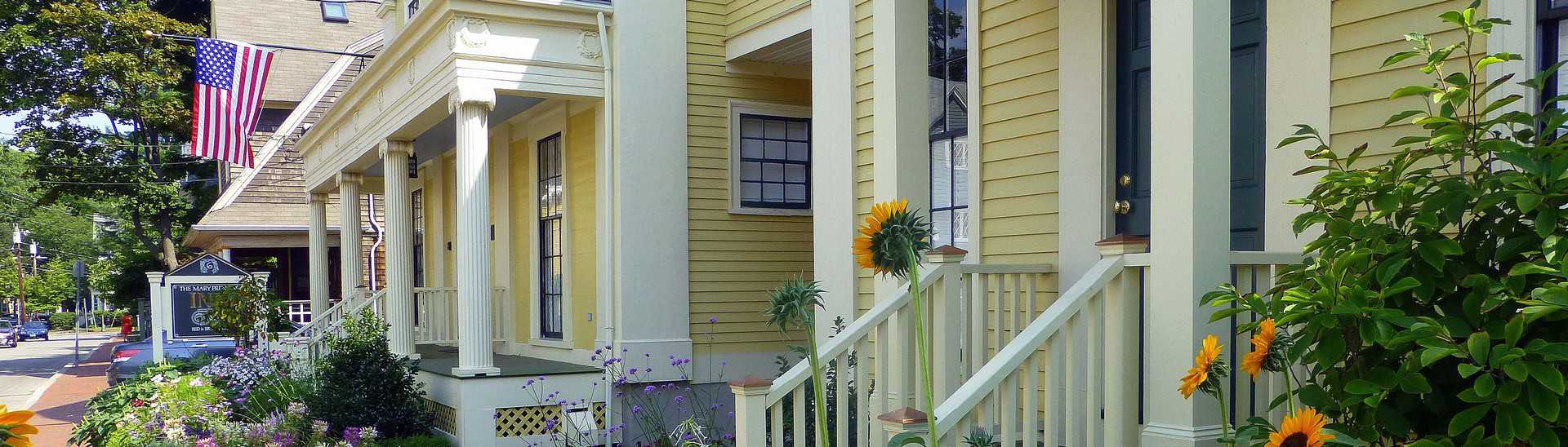 Exterior of yellow house along street with white pillars