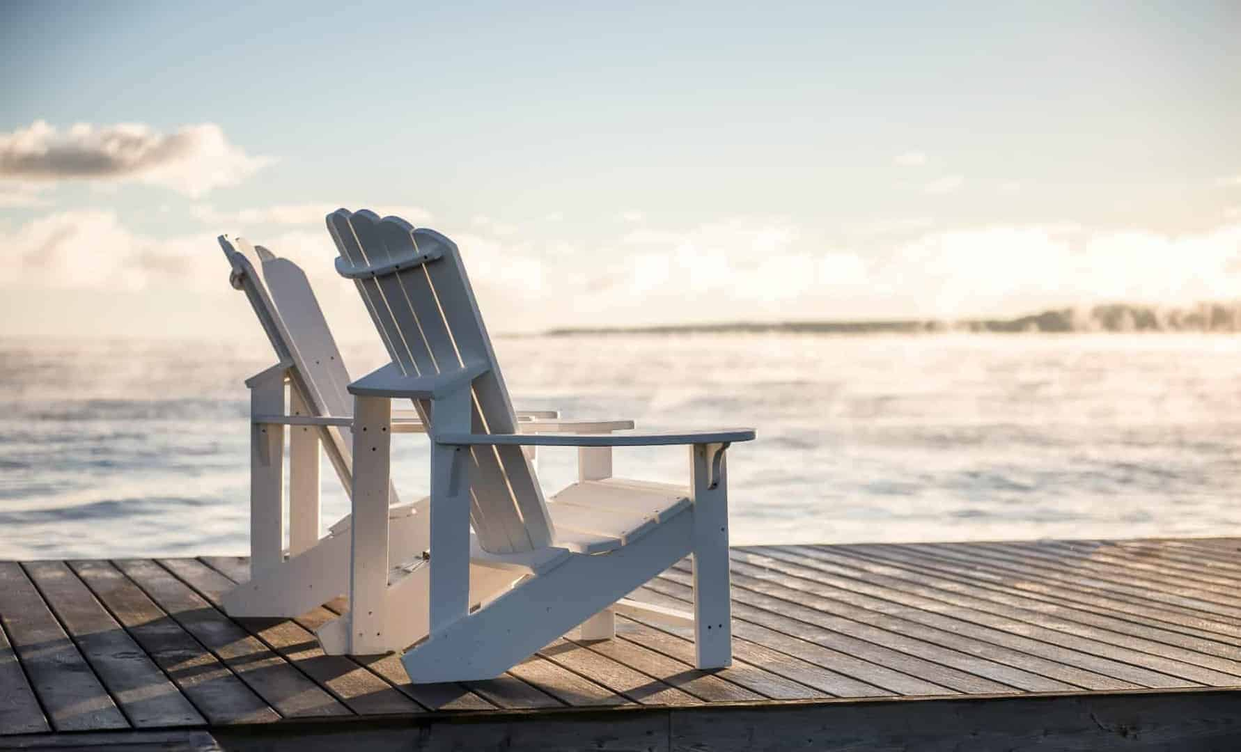 Two empty chairs in front of water