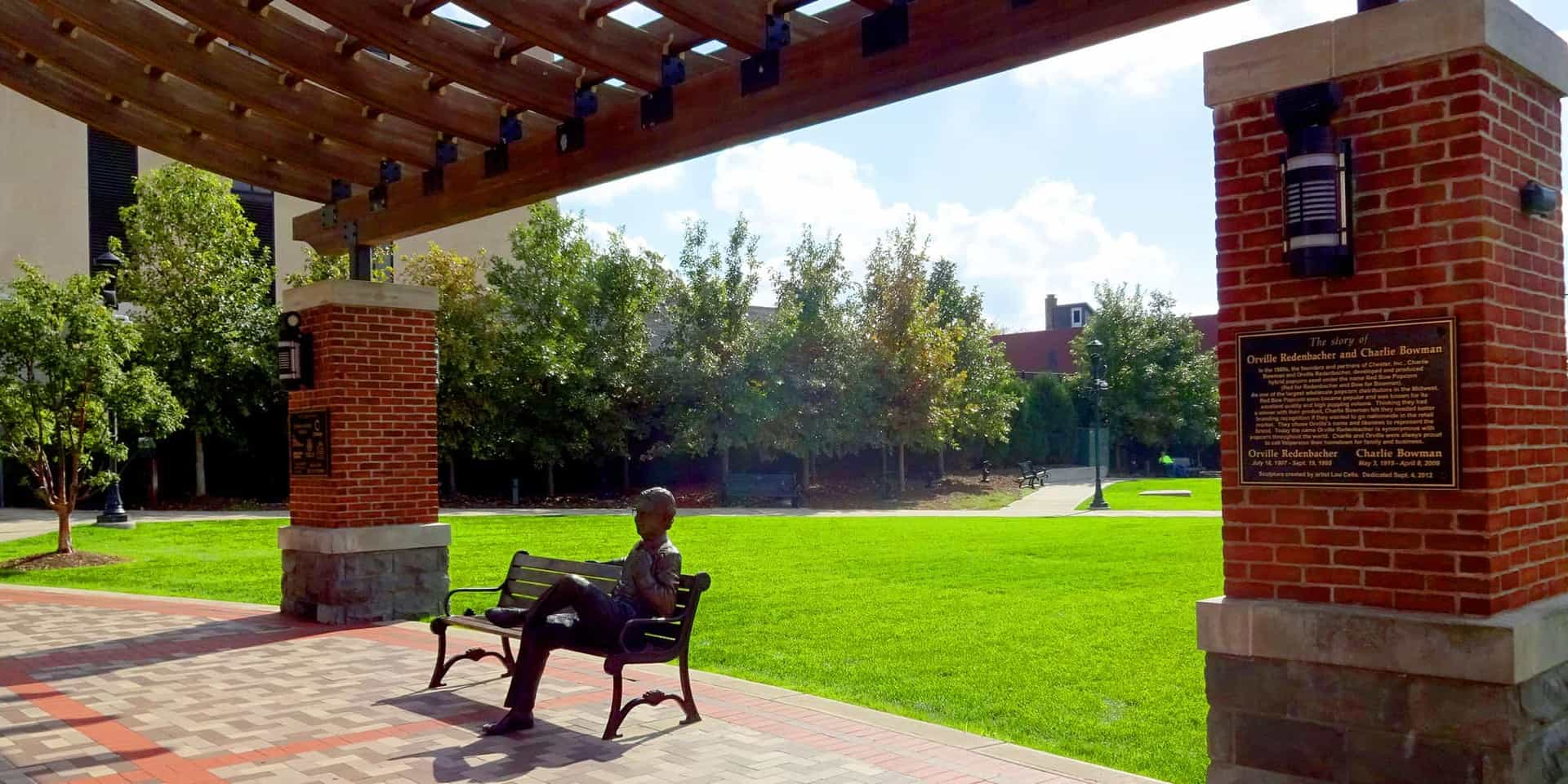 Bronze statue of man sitting on park bench under pergola
