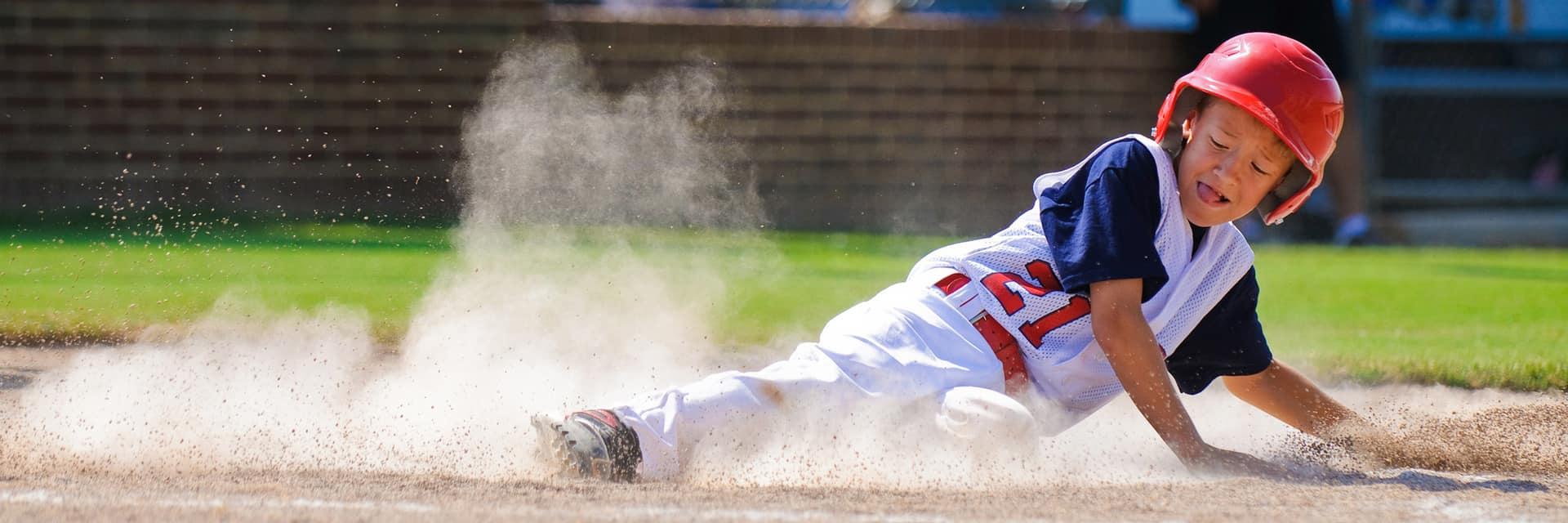 Child sliding into base playing baseball