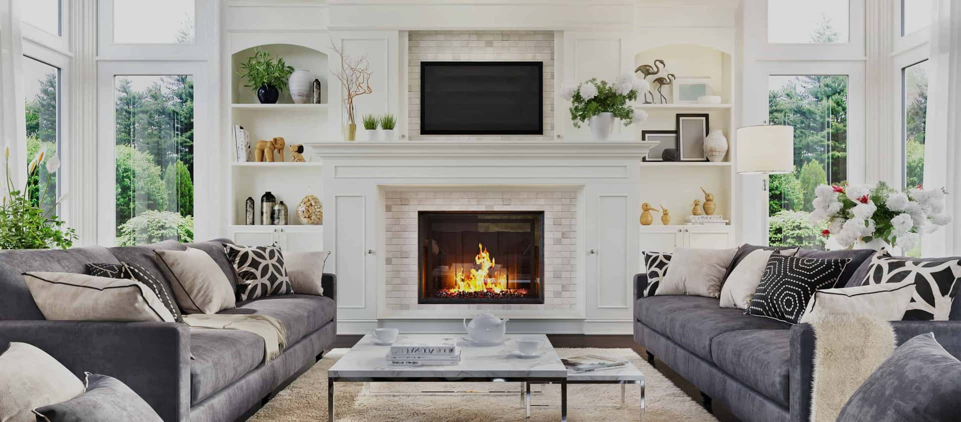 large living room in luxury home with fire burning in the fireplace