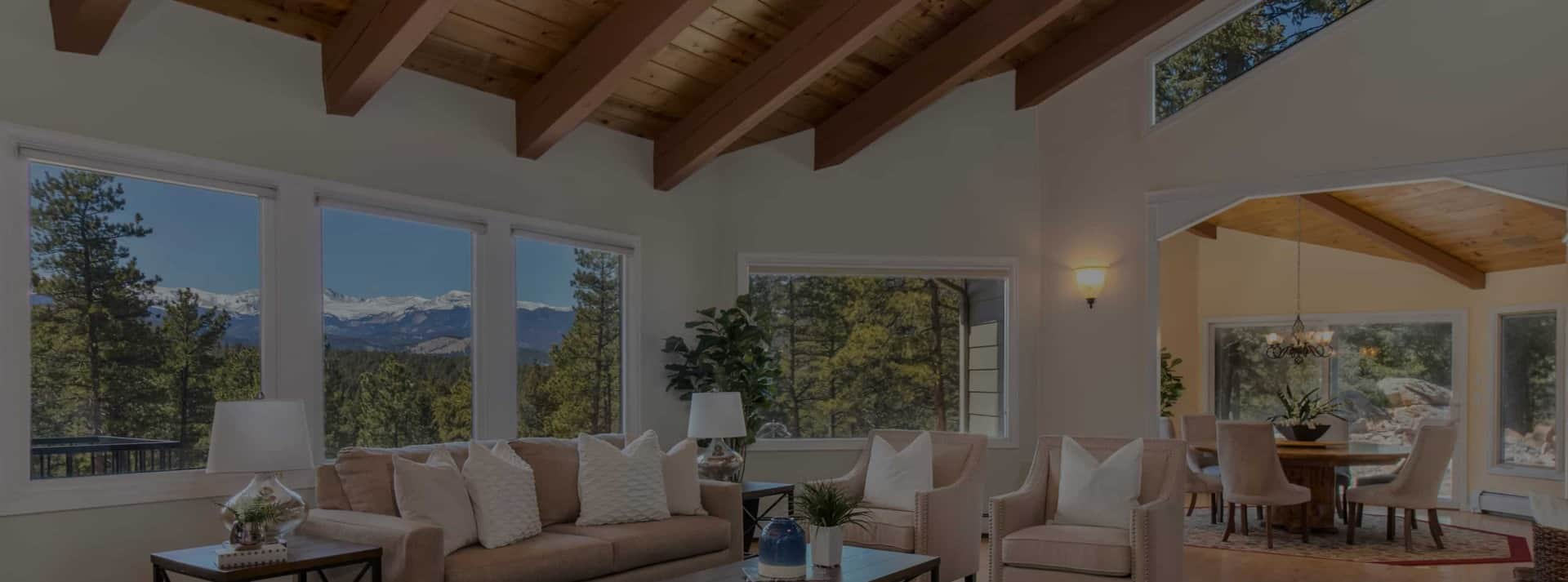 interior of luxury home with exposed beams, vaulted ceilings, and large windows.