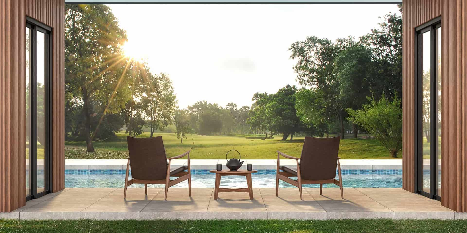 modern chairs outside modern house on patio looking over pool in backyard