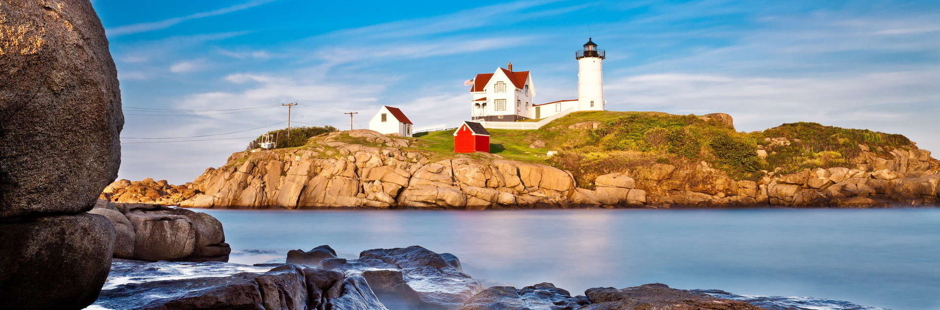 Historic lighthouse along rocky cliff in Maine.