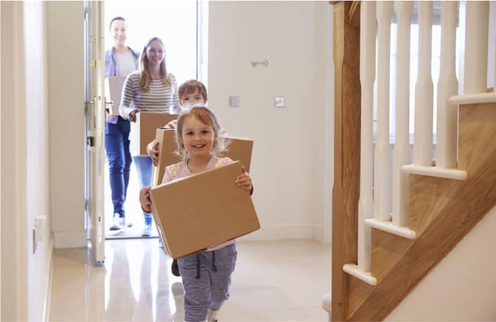 children carrying moving boxes into empty house