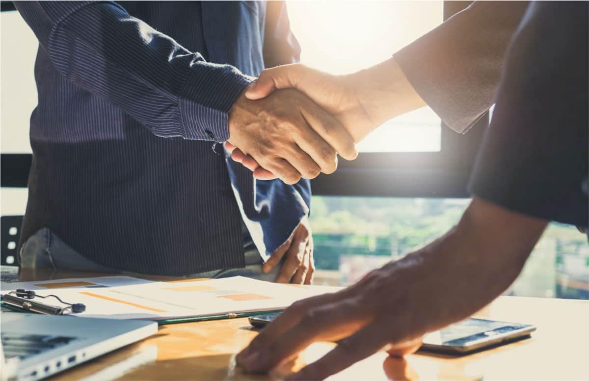 men shaking hands in office.